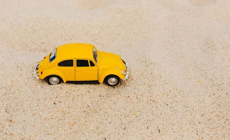 Miami, FL, USA - July 13, 2019: Yellow Small Toy Car on nature background. Retro car on Beach and Sand background. Summer vacation concept Редакционное