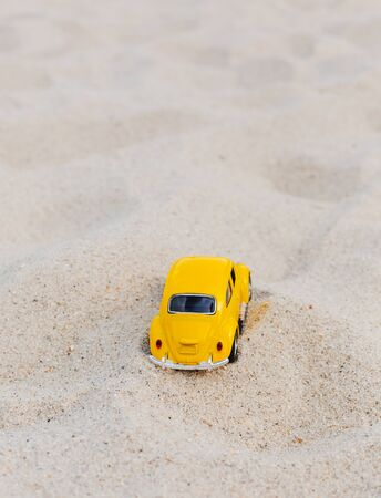 Miami, FL, USA - July 13, 2019: Yellow Small Toy Car on sand nature background.  Summer vacation concept. Copy Space