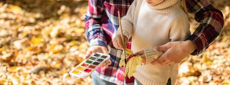 Cute little girl with her mother help drawing with paint autumn leaves outside. Park and Autumn Leaves on a Background. Autumn season concept.