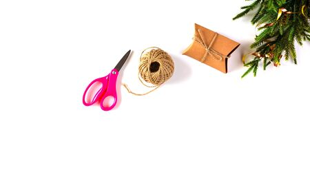 Christmas handmade craft paper gift box, fir branch, rope, scissors on White Background. Winter Christmas Holiday Concept. Happy New Year Flat Lay composition Banco de Imagens