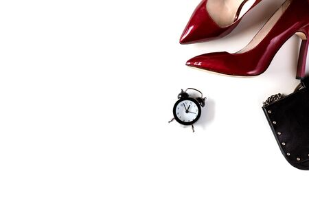 Top view of woman fashion red high heels, black purse and Alarm clock on white background. Party date night conception. Flat lay copy