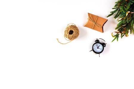 Christmas handmade craft paper gift box, fir branch, rope, alarm clock on White Background. Winter Christmas Holiday Concept. Happy New Year Flat Lay composition