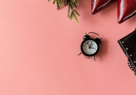 Top view of woman fashion red shoes, black purse and Alarm clock fir tree branch pink background. Party date night conception. Flat lay copy Banco de Imagens
