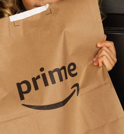 Miami, FL, USA - August 6, 2019:  Amazon Prime package in a hands in at apartment door. Amazon is an online company and is the largest retailer in the world.Amazon Prime is a service from Amazon which delivers parcels fast, in 1 day