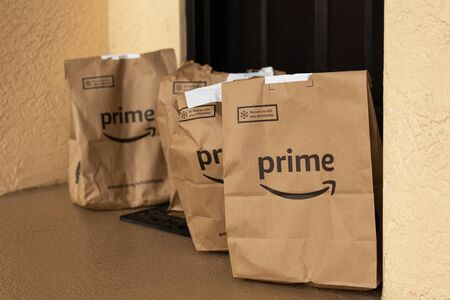 Miami, FL, USA - August 6, 2019: Image of  an Amazon Prime packages at apartment door.Amazon is an online company and is the largest retailer in the world.