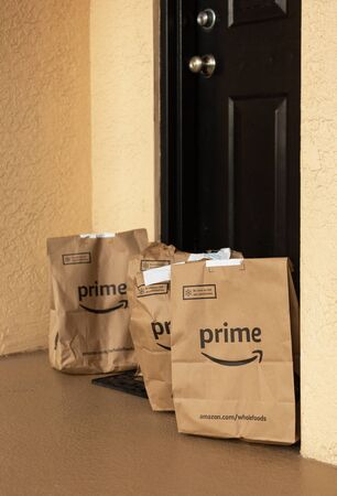 Miami, FL, USA - August 6, 2019:  Amazon Prime packages at apartment door. Amazon is an online company and is the largest retailer in the world.Amazon Prime is a service from Amazon which delivers parcels fast, in 1 day Редакционное