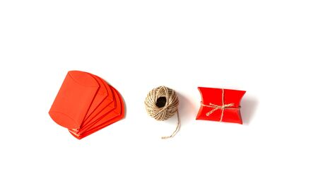 Preparing for Christmas, New year, packaging gifts: Red Packages and rope on a white background. Handmade gift on white background. Holiday Concept. Banco de Imagens