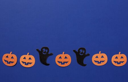 Creative composition of Halloween paper decorations made of ghost and pumpkins on dark blue background. Halloween concept. Minimal Flat lay, top view. Copy Space for text