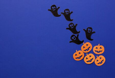 Creative composition of Halloween paper decorations made of ghost and pumpkins on dark blue background. Halloween concept.  Flat lay, top view. Copy Space for text