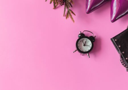 Top view of woman fashion pink shoes, black purse and Alarm clock on  pink color with neon. Party date night conception.Pink color trend concept. Copy Space for Text