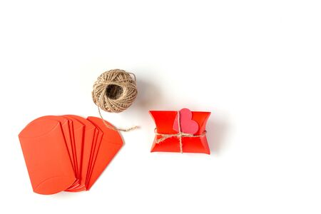 Image of Preparing for Christmas, New Year, packaging gifts: Red Packages and rope on a white background. Handmade gift on white background. Holiday Concept.
