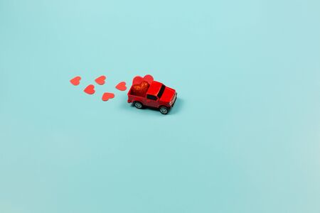 Valentines Day Concept. Miniature red toy car with red hearts