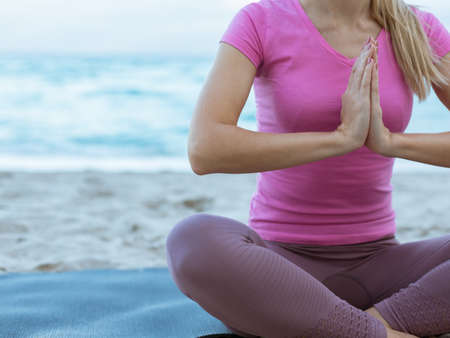Caucasian Young Woman Doing Yoga at the Beach, Ocean on a background. Woman in Sportswear Relaxing Outdoor. Health People Concept. Close up view. Фото со стока
