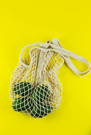 Avocado in a white eco net bag on a yellow background. Hass avocado in zero waste net bag. Plastic free concept. Copy Space Фото со стока