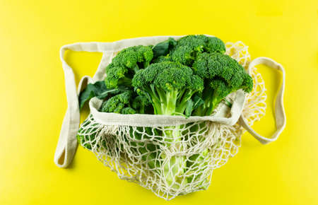 Fresh Broccoli in a white eco net bag on a yellow background. Hass avocado in zero waste net bag. Plastic free concept. Copy Space