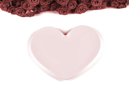 Table setting for Valentines Day with beautiful red roses and pink plate in the shape of a heart on white background.Valentines day dinner concept.