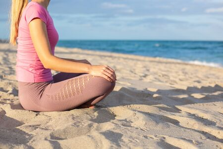 Caucasian Young Woman Doing Yoga at the Sandy Beach, Ocean on a background. Woman in Sportswear Relaxing Outdoor. Health People Concept. Copy Space