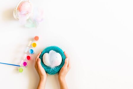 Childs hands holding blue basket or nest with Easter eggs on white background. Coloring eggs for easter t at home. Happy Easter concept. Copy Space