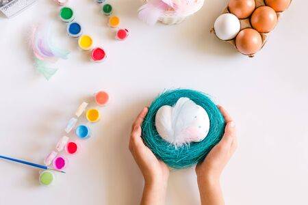Childs hands holding blue basket or nest with Easter eggs on white background. Coloring eggs for easter t at home. Happy Easter concept.