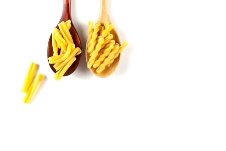 Two types of italian pasta concept. Raw gemelli, casarecce in wooden spoons on white background. Top view, copy space. Фото со стока