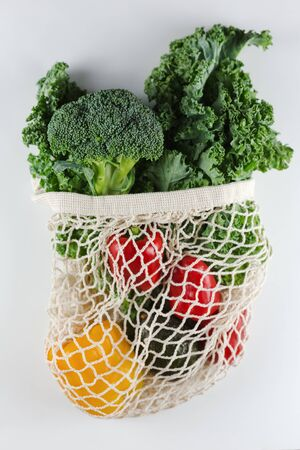 Eco friendly mesh bag with organic vegetables: Kale salad, broccoli, avocado, bell peppers on a white background. Zero waste concept. Healthy clean eating diet and detox. Top view