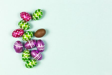 Colorful chocolate easter eggs on blue background. Small Chocolate eggs in a foil. Traditional Easter sweet. Copy Space