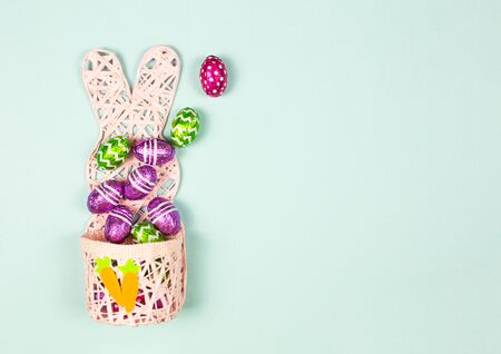 Easter basket full of Colorful chocolate easter eggs on blue background. Small Chocolate eggs in a foil. Traditional Easter sweet. Copy Space