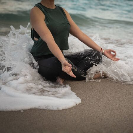 Young Woman Doing Yoga at the Ocean, the wave covered her. Attractive Woman in Sportswear Relaxing Outdoor. Health People Concept. Copy Space. Close up view
