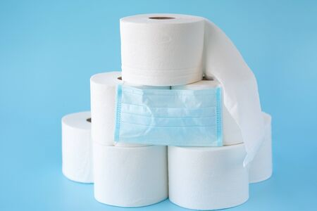 Toilet paper stacked rolls, medicine mask on a blue background. Items that buiyng in panic. Toilet paper crisis due to coronavirus COVID-19 quarantine. Copy space Фото со стока