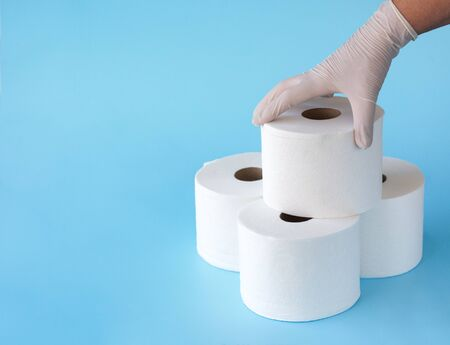 Female hand in medical gloves takes a roll of toilet paper from a folded tower of rolls on blue