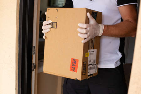 Miami, FL, USA - March 25, 2020: Amazon Prime package in a hands in at apartment door. Quarantine due Coronavirus. Amazon is an online company and is the largest retailer in the world.