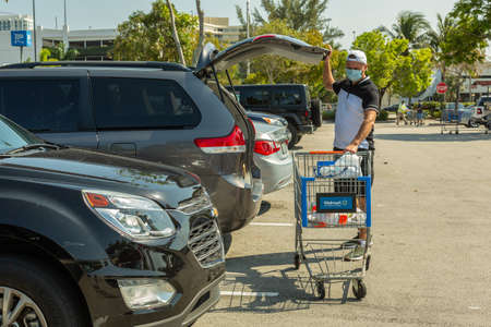 Miami, FL, USA - March 26, 2020:Man wearing medical mask on Walmart store parking space. Walmart is the world's third largest public corporation. Quarantine due Coronavirus time.