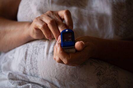 Pulse Oximeter On a female finger. Woman using Oximeter. Healthy Concept. Due Coronavirus medical equipment.