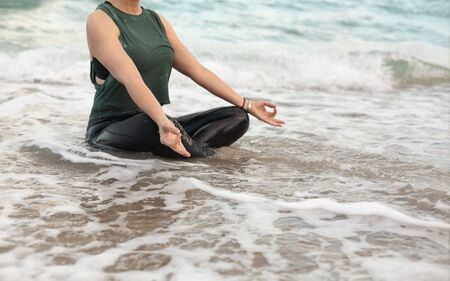 Young Woman Doing Yoga in the Ocean, the wave covered her. Attractive Woman in Sportswear Relaxing Outdoor. Health People Concept. Copy Space Фото со стока