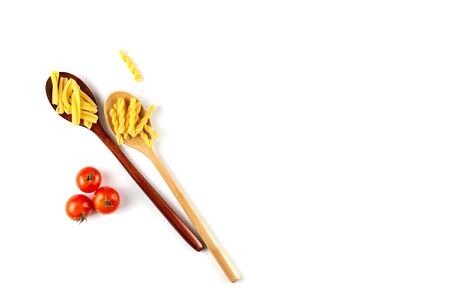 Two types of italian pasta concept. Raw gemelli, casarecce in wooden spoons, tomatos on white background. Top view, copy space.