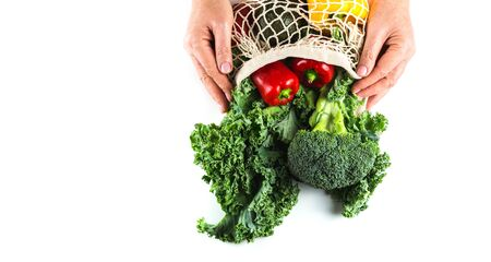 Womans hands holding Eco friendly mesh bag and organic vegetables: Kale salad, broccoli, avocado, peppers on white background. Flat lay. Zero waste concept. Healthy clean eating diet. Copy space