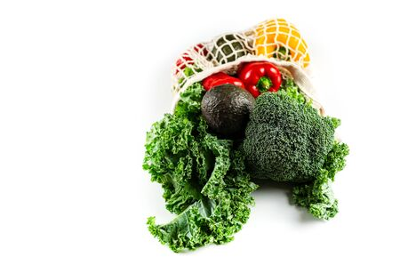 Eco friendly mesh bag with organic vegetables: Kale salad, broccoli, avocado, bell peppers on a white background. Zero waste concept. Healthy clean eating diet and detox. Top view, Copy space
