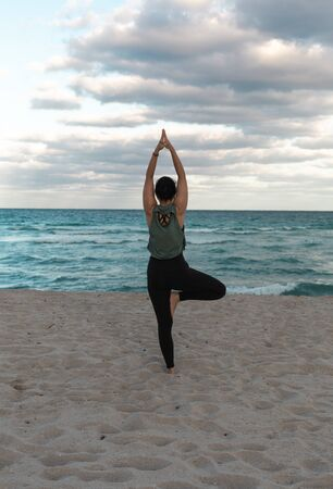 Attractive Woman doing yoga exercise at sandy beach, standing in Vrksasana Posture, Tree Pose. Woman standing on one leg in yoga pose. Copy Space Фото со стока