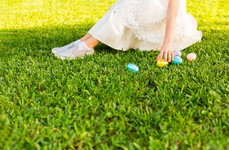 Little girl in a beautiful white dress hunting for easter egg on Easter day. Child having fun outdoor. Kid playing with eggs on green grass. Spring holidays concept. Copy Space for text Фото со стока