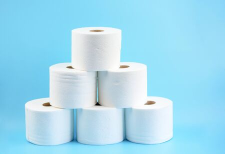 Toilet paper stacked rolls on a blue background.Toilet paper crisis due to coronavirus COVID-19 quarantine. Copy Space. Фото со стока