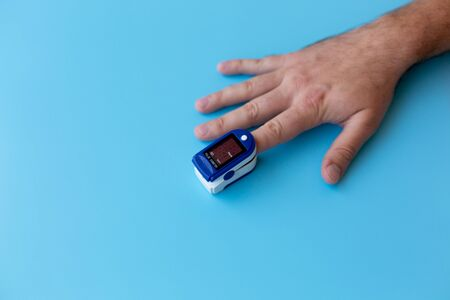 Pulse Oximeter On a male finger. Man using Oximeter. Healthy Concept Фото со стока