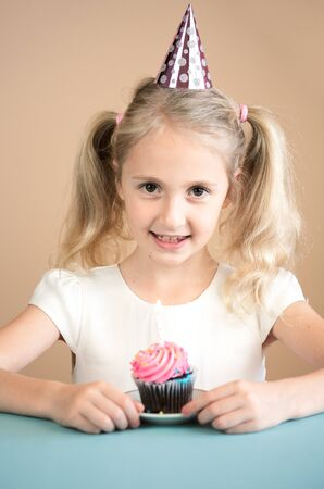 Portrait Caucasian Girl wearing birthday hat  with birthday cake. Happy Birthday Concept. Фото со стока
