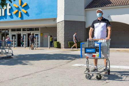 Man wearing medical mask on Walmart store parking space. Quarantine due Coronavirus time. Editorial