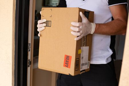 Doorstep package in a male hands in at apartment door. Quarantine due Coronavirus. Concept of service delivery.
