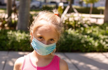 A little girl walks in the park in a medical face mask. A little girl walks through an empty city and covers her face with a mask from a coronavirus. Quarantine due Coronavirus time. Copy Space.