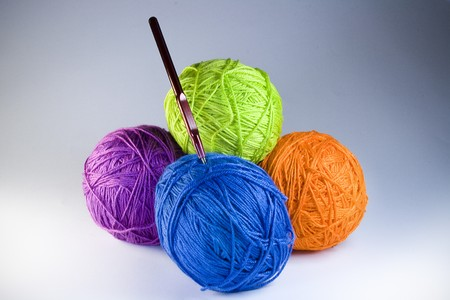 silk wool: Four multi-coloured balls with threads and a needle