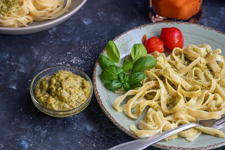 Tagliatelle cooked aldente with pasta pesto. Next to the bowl with sauces, a glass of fresh carrot. The noodles are decorated with green sprigs of basil. Healthy life experience. Proper nutrition.