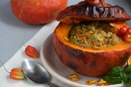 Baked pumpkin stuffed with vegetable stew with rice. Nearby are the berries of physalis, and in the background is a fresh orange tavern. healthy lifestyle. Proper nutrition. Diet. Banco de Imagens