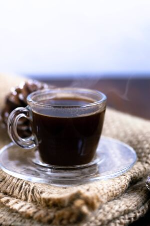 Coffee in a transparent cup. Hot, invigorating drink. Near cones in sparkles, coffee beans are scattered. Reklamní fotografie