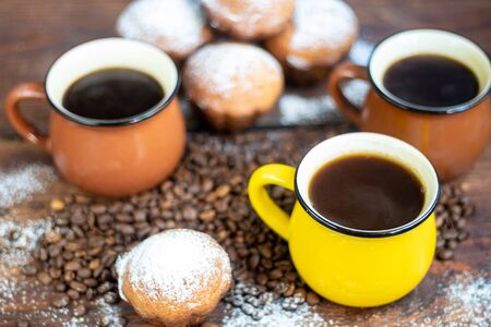 Coffee in brown cups. Hot, invigorating drink. Coffee beans are scattered nearby. In the background homemade cupcakes.